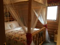 Handcrafted queen size log canopy beds in each cabin